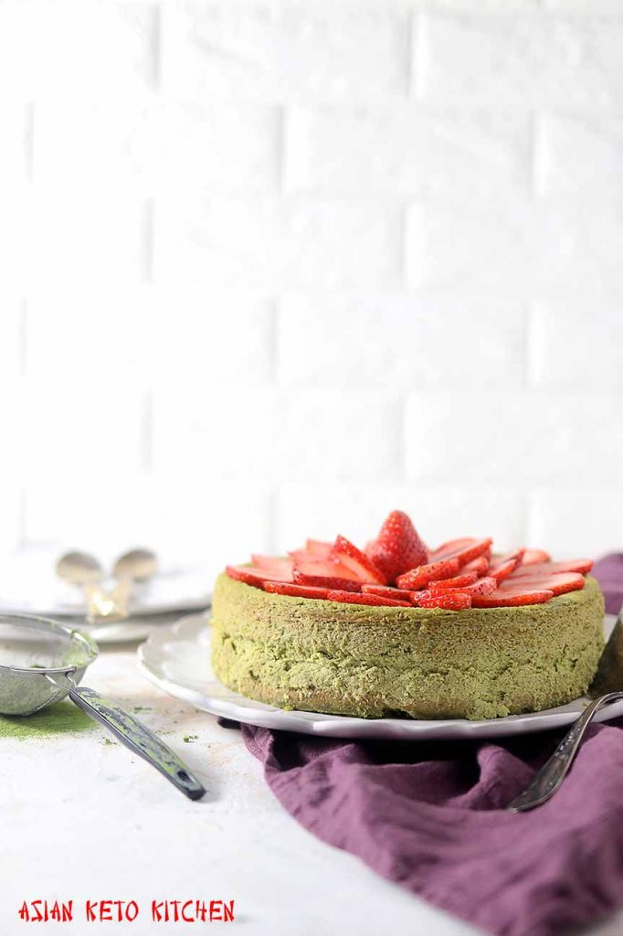A whole Japanese matcha cheesecake topped with sliced strawberries.