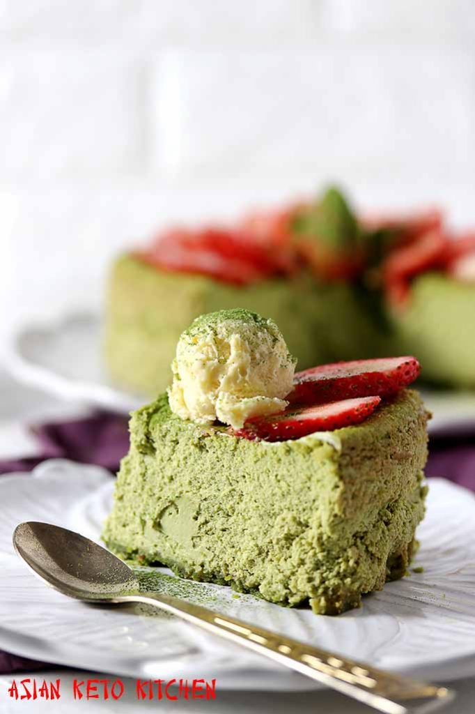 A spoonful of sugar free ice cream topped over a Japanese green tea cheesecake with strawberry slices.