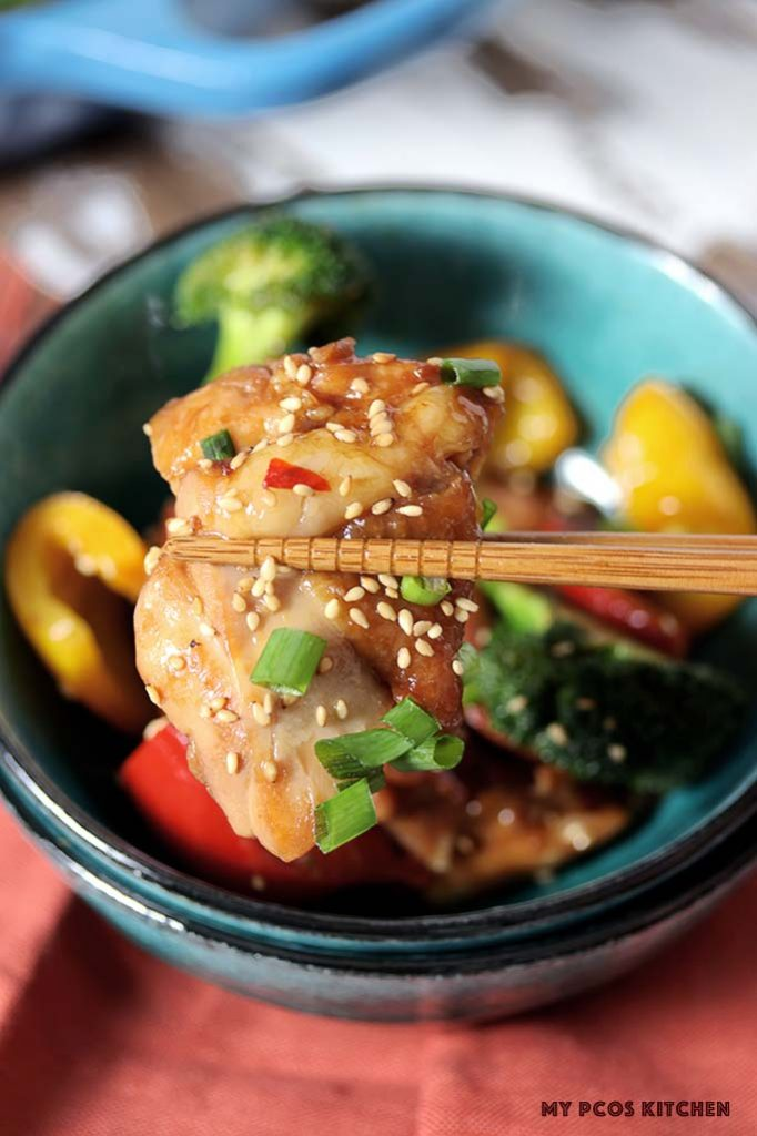 Chopsticks holding a piece of juicy teriyaki chicken with sticky sauce that's all sugar free!
