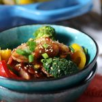 Sugar free teriyaki chicken with vegetables in a green bowl.