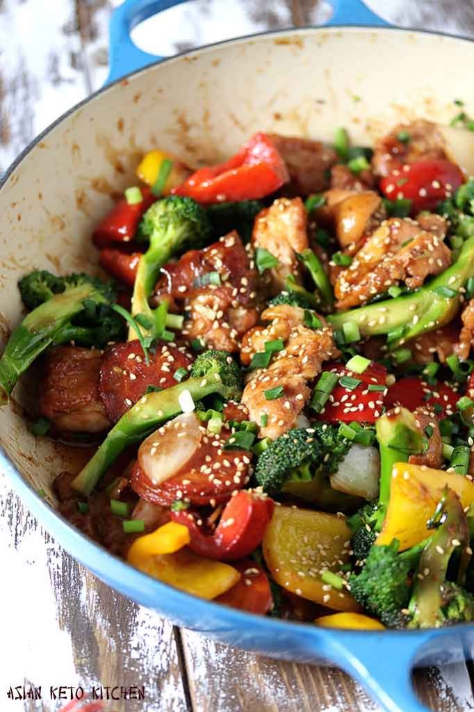 Japanese teriyaki chicken stir fry with vegetables in a blue le creuset skillet.