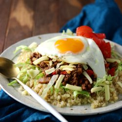 A plate full of taco rice ingredients made with cauliflower rice, taco meat, lettuce, tomato and cheese.